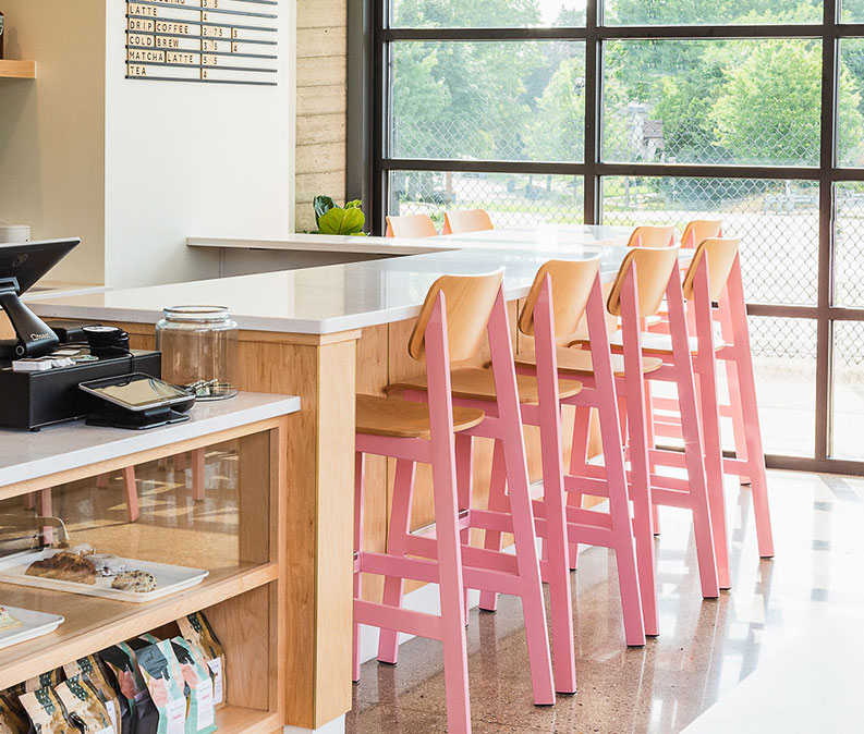Sadie II Barstool in pink and natural at a modern coffee shop