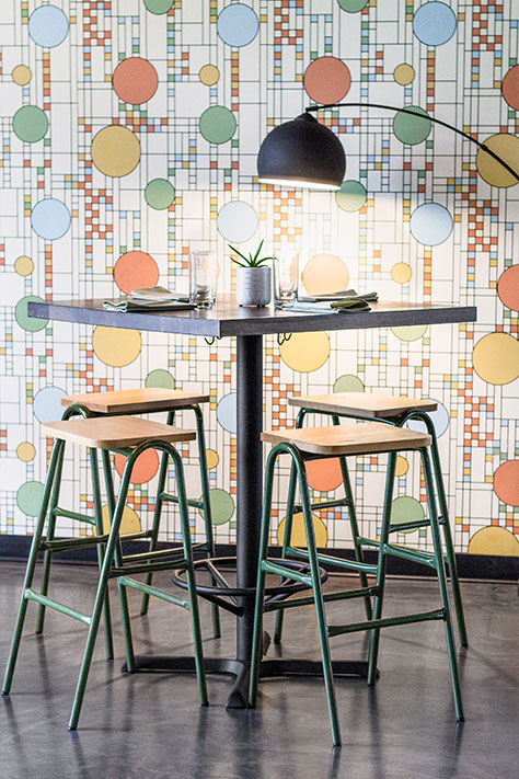 Olive Green Bar Stools against patterened wallpaper inside of a restaurant