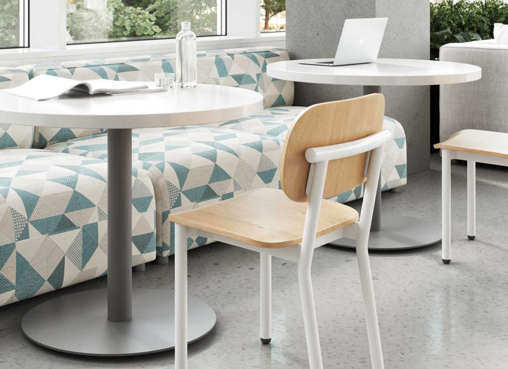 Modern Dining Chair with White Frame and Natural wood seat and back in a university cafeteria at a table.