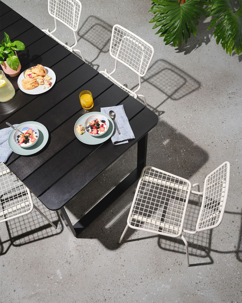 Overhead view of the bowen outdoor dining table with white Opla chairs