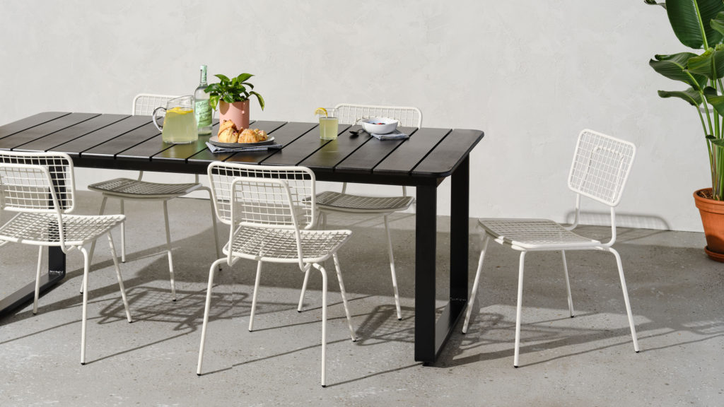 Black outdoor dining table with white outdoor stacking chairs